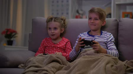 sisters : Brother joking with sister covering with blanket, kids playing online game night