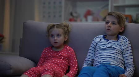 мультфильмы : Little boy and girl watching horror movie at night, sitting on sofa, leisure Стоковые видеозаписи