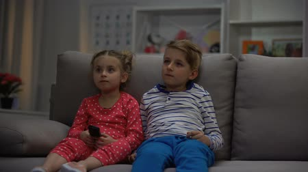 abriu : Small children watching television surprised by opened door, parents control