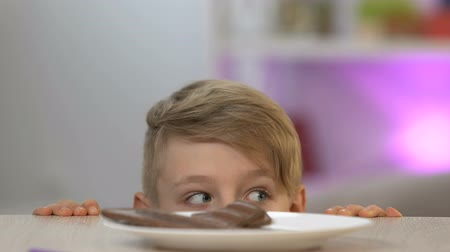украсть : Boy appearing from under table and stealing piece of chocolate bar, sweet-tooth