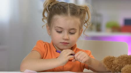 imaginário : Sweet little girl painting and showing picture to toy teddy bear, playing