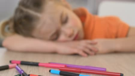 fárasztó : Girl sleeping on table in kindergarten, exhausted after tiring art lesson, close