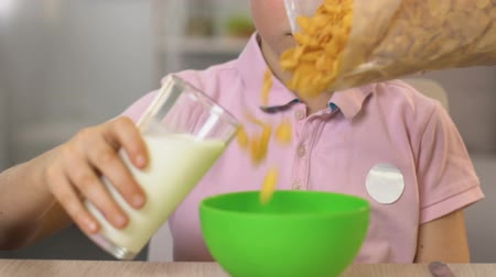 flocos de milho : Schoolboy pouring milk in bowl with cereal, tasty healthy breakfast, close up