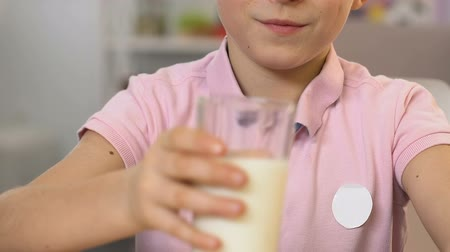cálcio : Hand pouring milk in glass, boy drinking it with pleasure, healthy meal, vitamin Vídeos