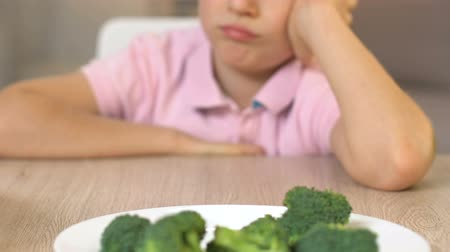 refusal to eat : Upset boy looking at broccoli with disgust, refusal to eat, vegetarian lifestyle