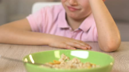 refusal to eat : Schoolboy refusing to eat oatmeal, feeling disgust, healthy nutrition for kids