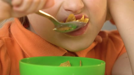 corn flakes : Cute little girl eating cereal and milk with appetite for breakfast, close-up