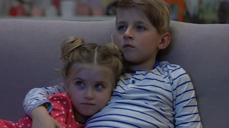 щит : Tired brother and sister watching tv at night, boy protects scared girl, horror