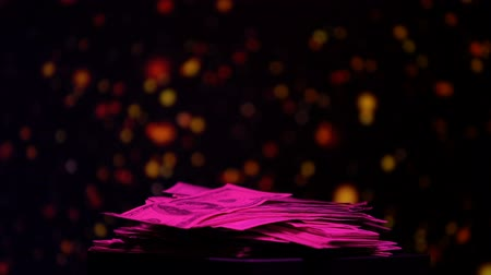 шансы : Pile of dollars illuminated by pink light, earnings in nightclub, dirty money