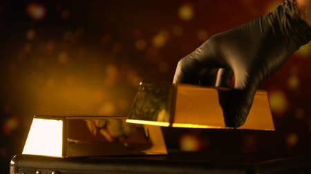 hoard : Hand in glove putting gold bullion, evaluation of precious metals, pawnshop
