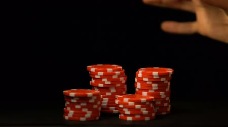 sin limites : Hand putting red chips isolated on black, gambling addiction, casino business