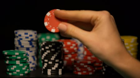 шансы : Hand choosing red chip among stacks of tokens, casino game odds, lucky bet