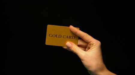 prestiž : Hand showing gold card on black background, status vip, unlimited finances