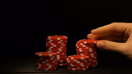 шансы : Hand putting poker chips isolated on black, temptation for all-in bet, addiction