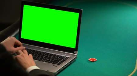 шансы : Man using online betting services on laptop, holding lucky chip, green screen Стоковые видеозаписи