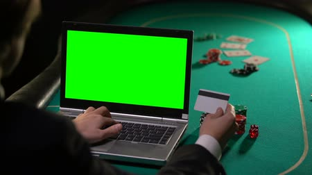 шансы : Man paying poker bet with credit card, using laptop green screen, online winning