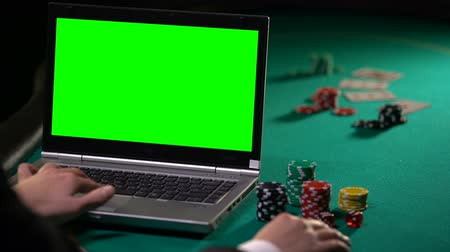 piyango : Man playing poker online on laptop, betting on gambling sites, green screen