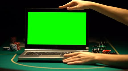 ruletka : Female hands opening laptop, poker chips around, online casino advertising