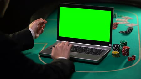 esély : Man holding lucky chip and betting on gambling services on laptop, green screen