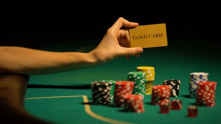шансы : Hand holding gold card, gambling chips on table, illegal casino for VIP-clients
