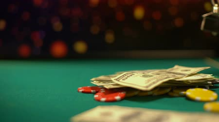 arriscado : Risky poker player putting chips, money and house keys on table, all-in bet
