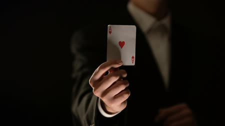 esély : Tricky poker player getting ace of heart from sleeve, illegal game, cheating