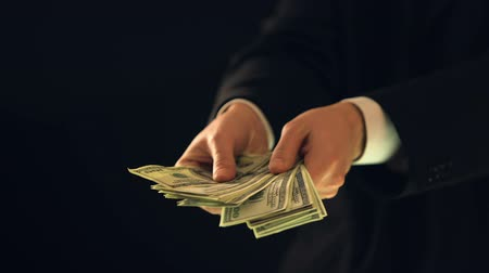 reaching : Man in suit counting money against dark background, illegal business deal