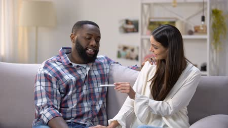 fertilidade : Woman showing pregnancy test to happy Afro-American boyfriend, positive result