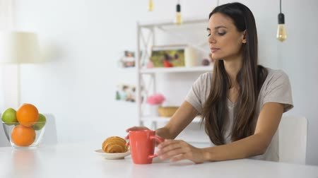 gevoelig : Woman having lunch, drinking coffee with croissant feeling toothache from sweets