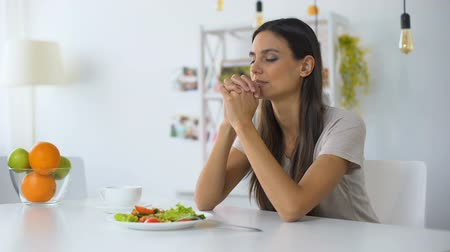 áldás : Young woman praying, blessing God for dinner, eating healthy vegetarian salad Stock mozgókép