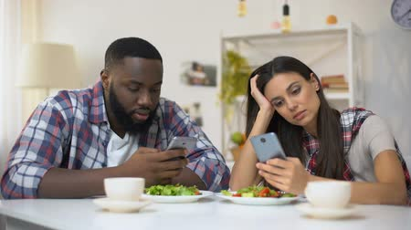 lack : Offended mixed-race couple using smartphones during lunch, misunderstanding