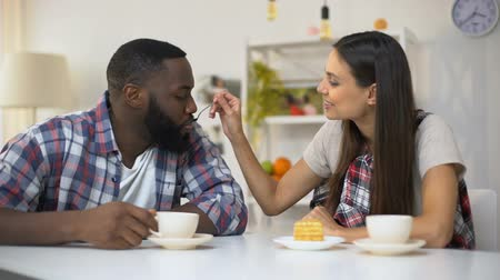 tort weselny : Young housewife feeding Afro-American husband with sweet cake, romantic lunch