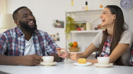 multiethnic : Mixed-race couple having lunch with cake, fooling around together, relations