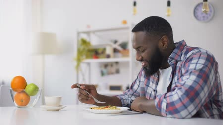 unpleasant smell : African-American man eating spoiled spaghetti on lunch, stomach disease, nausea