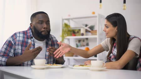 přestupek : Young multiethnic couple arguing during lunch at home, man leaving crying woman