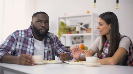 sertés : Annoyed multiracial couple having fight during lunch, family relations, conflict