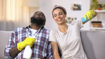 caseiro : Mixed-race couple in gloves with cleanser spray, happy about made housework
