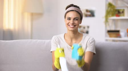 disinfectant : Smiling female in gloves showing cleansing spray and sponge to camera, housework