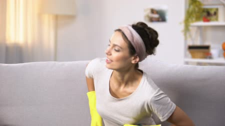 housekeeper : Smiling housewife in gloves sitting on sofa and looking at camera, household