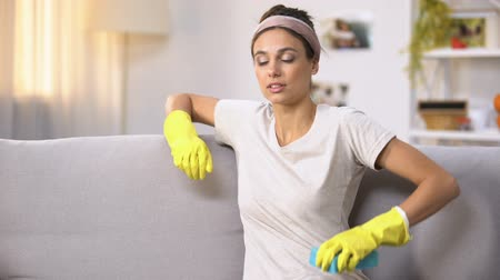tiredness : Exhausted woman in gloves sitting on sofa, relaxing after house cleaning work Stock Footage