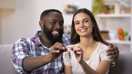 multietnikus : Cheerful multiethnic couple holding house key chain, mortgage for young people Stock mozgókép