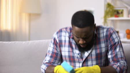 disinfectant : Exhausted black man in gloves sitting on sofa, relaxing after house cleaning Stock Footage