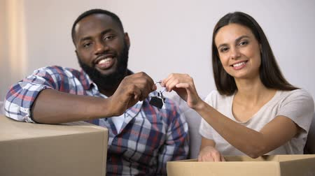 ailelerin : Happy multiracial couple holding carton boxes and house key chain, relocation Stok Video