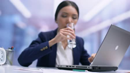 professional wellness : Busy female employee drinking water from glass sitting office table, refreshment Stock Footage