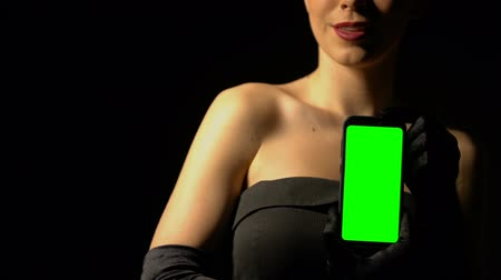kaszinó : Woman in elegant dress showing smartphone with green screen, online casino