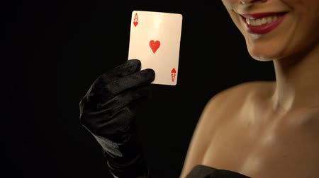 kazık : Smiling woman showing ace of hearts into camera, isolated on black background