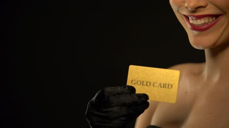 пари : Elegant woman showing gold card into camera isolated on black background