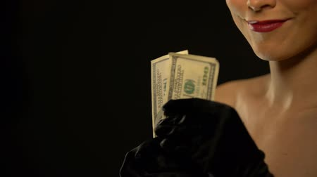 kochanka : Smiling lady showing bunch of dollars into camera, isolated on black background Wideo