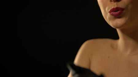 prostituta : Elegant female in gloves sending air kiss to camera isolated on black background