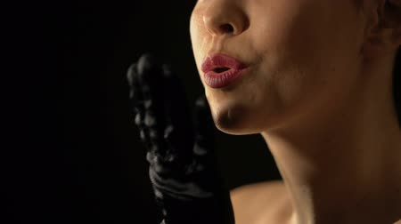 wizaż : Smiling lady in black gloves sending air kiss to camera against black background Wideo